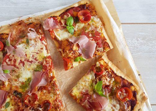 Pizza Caprese met tomaat, mozzarella, pesto en rauwe ham